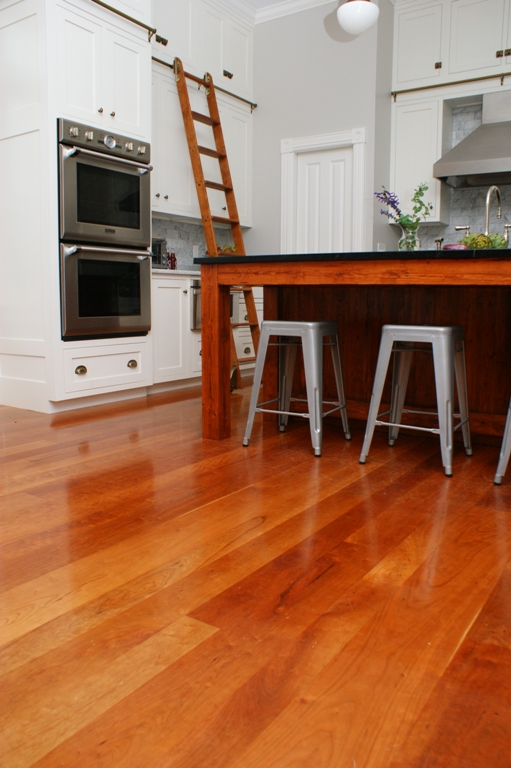 Warm colored cherry wood floors brighten an all white kitchen.
