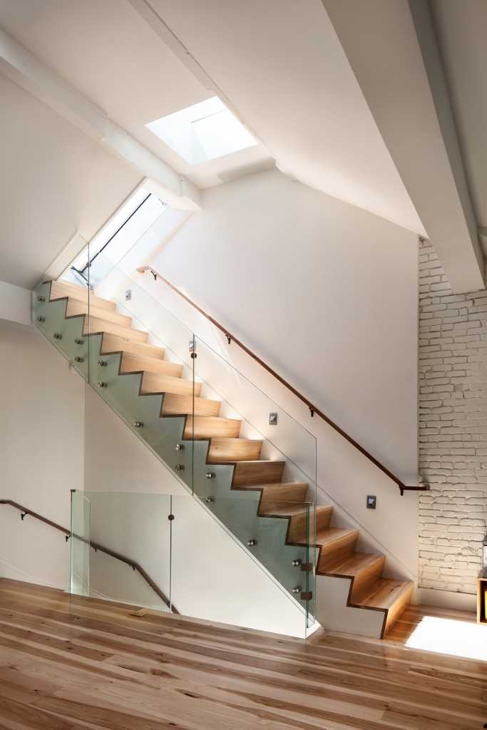 Wood flooring warms up a white kitchen for House plans with stairs in kitchen