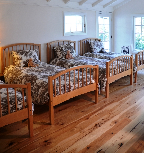 This California retreat's bunkhouse-style bedroom needed a wood floor that could accommodate heavy foot traffic, so the homeowners chose wide plank Hickory flooring.