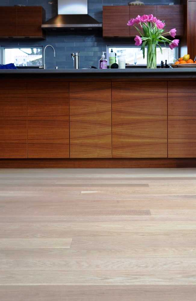 Figure 6: Light colored select grade White Oak (Hull wide plank floor #211) with five inch plank widths, finished with a water-based poly. The floors provide a pleasing contrast to the kitchen's darker cabinetry.